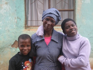 Maria and two of her granddaughters outside their home